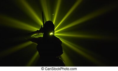 Dark silhouette of a woman posing with a sword in the center of yellow spotlight. Bottom view. Close up in slow motion