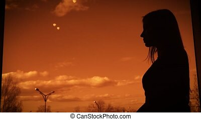 Dark silhouette of a woman standing in profile on twilight backcloth near the window. Outline of female body against orange sunset sky with white clouds and trees in the background.