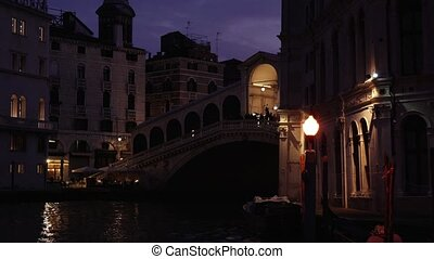 Dark silhouette of famous Rialto Bridge over calm black water surface of Grand Canal under boundless violet twilight sky