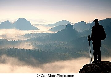 Dark silhouette of hiker with poles in hand. Sunny spring...