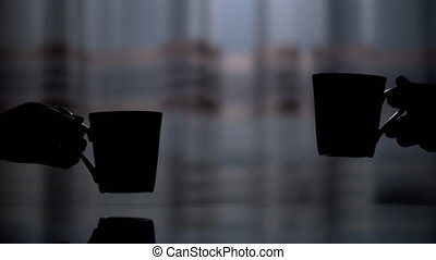 Dark silhouette of two ceramic cups, a man's and a woman's hand picks them up from the table