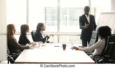 Dark-skinned businessman giving presentation to partners at meeting in boardroom
