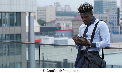 Dark-skinned businessman text messaging outdoors - Busy...