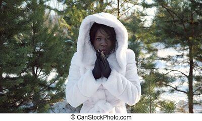 dark-skinned girl trembles with cold and warms hands - sad ...