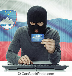 Dark-skinned hacker with flag on background holding credit ...
