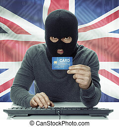 Dark-skinned hacker with flag on background holding credit card - United Kingdom