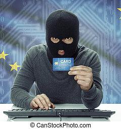 Dark-skinned hacker with USA states flag on background holding credit card - Alaska