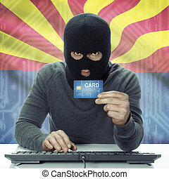 Dark-skinned hacker with USA states flag on background holding credit card - Arizona