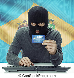 Dark-skinned hacker with USA states flag on background holding credit card - Delaware