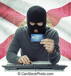 Dark-skinned hacker with USA states flag on background holding credit card - Florida