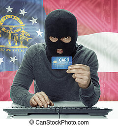 Dark-skinned hacker with USA states flag on background holding credit card - Georgia