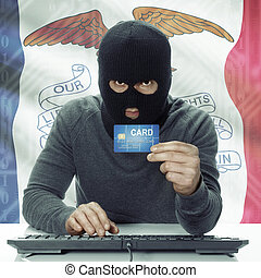 Dark-skinned hacker with USA states flag on background holding credit card - Iowa