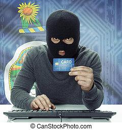 Dark-skinned hacker with USA states flag on background holding credit card - Kansas