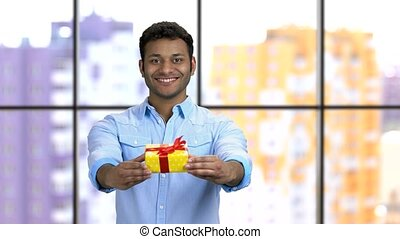 Dark-skinned hindu man giving gift box. Handsome cheerful guy wearing formal shirt with present for your birthday. Window background.