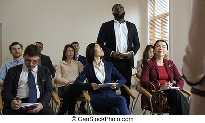 Dark-skinned man asking a question at training - Positive...
