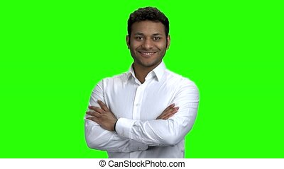 Dark-skinned man in white shirt on green screen.