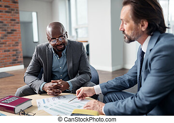 Dark-skinned man speaking with his lawyer sitting in the office