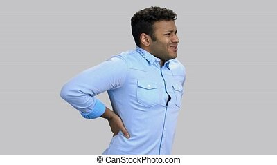 Dark-skinned man touching his back because of a sudden pain. Grey background.