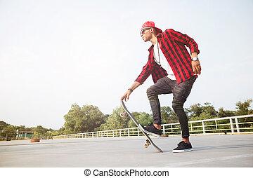 Dark skinned man wearing sunglasses skateboarding
