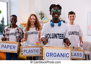 Dark-skinned teenager holding box with organic waste after sorting