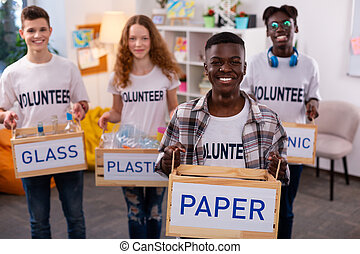 Dark-skinned teenager holding box with paper after sorting
