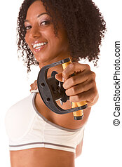 Dark skinned woman stretching using rubber band (selective focus on hand)