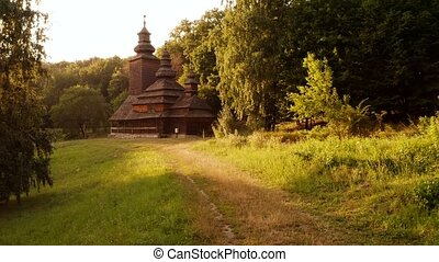 Dark spooky orthodox church in a forest. Trail pathway to a christian temple.