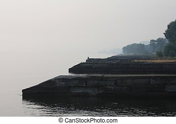 Dark stone pier in the fog and a fisherman in the early morning fishing. Thickening of fog, tension, loneliness. High dramatic tension. Fishing on the lake. A man sits on a cliff of a pier alone in the fog
