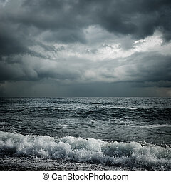 dark storm clouds and sea - dark storm clouds and waves on...