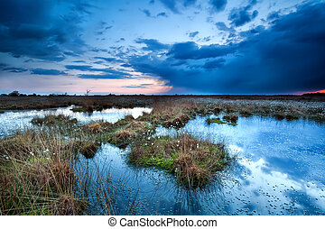 storm clouds over lake at sunset - dark storm clouds over...