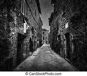Dark street in an old Italian town in Tuscany, Italy. Raining, black and white