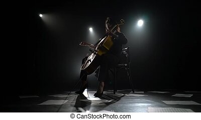 Dark studio girl playing the cello on the floor sheets of notes. Silhouette. Black smoke background