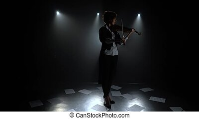 Dark studio girl playing the violin on the floor sheets of notes. Silhouette. Black smoke background