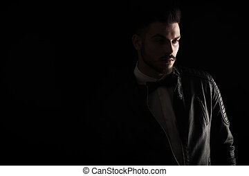 Dark studio shot of a young business man looking away from ...