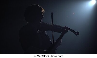 Dark studio with lanterns girl playing the violin . Silhouette. Black smoke background