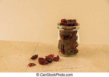 Dark, sun dried tomatoes in jar and scattered with copyspace.