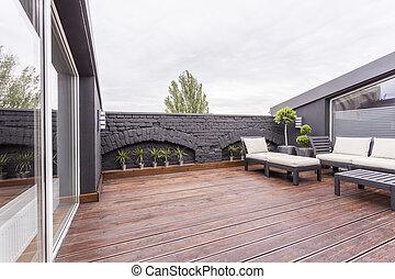 Dark terrace with garden furniture