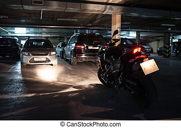 Dark underground parking area with black motorcycle with...