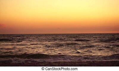 Dark waves crashing at sunset - The scene is split in half,...