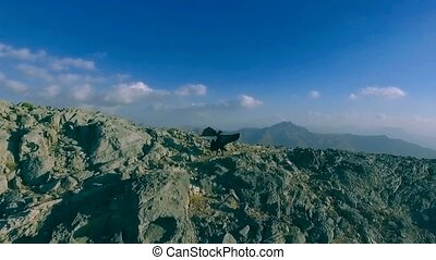 Dark witch young woman with isis wings is flying in the jebel jais mountains. Girl in zorro costume is practicing, exercising, waving cloak. Mystic lady dreams about freedom, game of thrones style