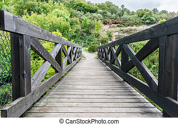 dark wooden bridge over river in a mountain forest