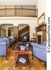 Dark wooden table between blue armchairs in luxury living room interior with sofa. Real photo