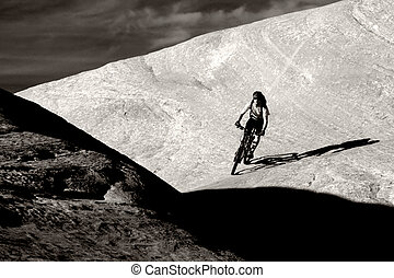 Darkness - A biker descending into the shadows on a trail ...
