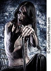 darkness - Gloomy vampire sitting at the night background....