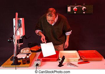 Darkroom printing - Photographer printing photos in a dark ...