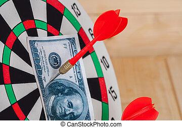 Dart arrow hitting in bullseye on dartboard with money