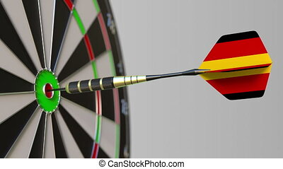 Dart featuring flag of Germany hits bullseye of the target....