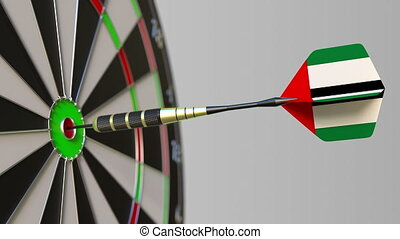 Dart featuring flag of the United Arab Emirates UAE hits bullseye of the target. Sports or political success related conceptual animation