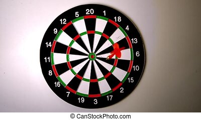 Dart hitting a bulls eye on dart board in slow motion