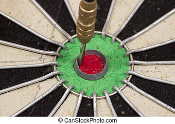 Dartboard with dart in the bull